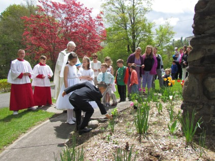 Flowers are placed at the feet of Mary by her newest children.